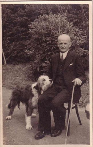 Mr Gimblett sitting in chair in garden with long-haired dog