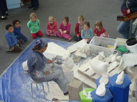 Children watching Wendy Hodder working on cat sculpture