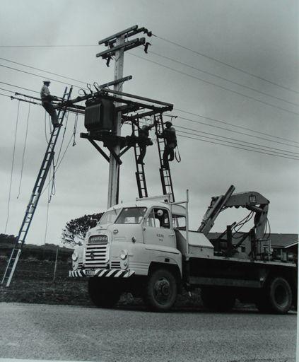 Linemen installing transformer on power pole, rural area