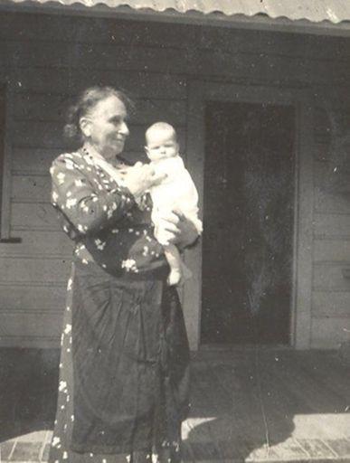 Elderly woman holding baby.