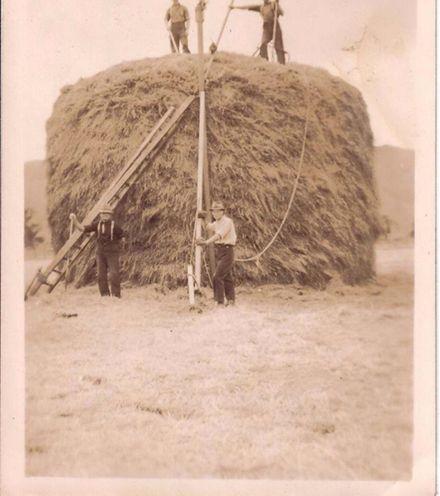 Men building haystack